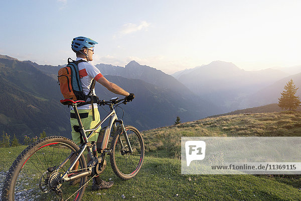 Rear view of mountain biker standing in the alpine landscape and looking at view during sunset  Zillertal  Tyrol  Austria