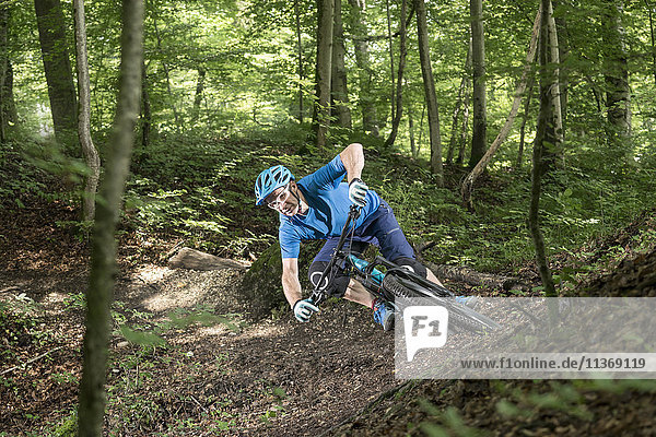 Mountain biker riding downhill in forest
