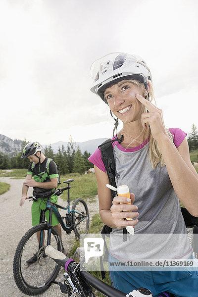 Mountain bikers applying sun cream  Kampenwand