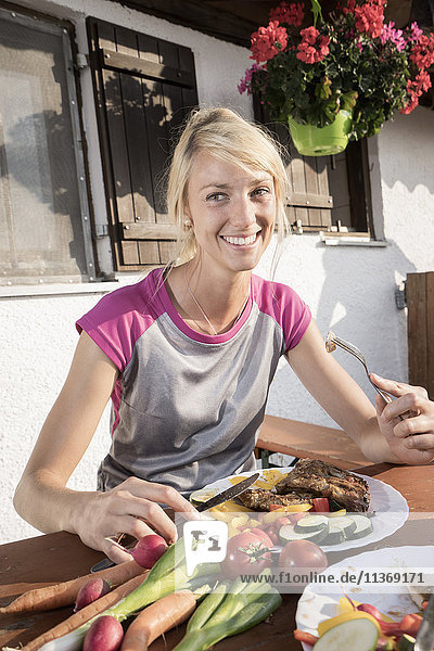 Young woman eating salad at alpine cabin  Kampenwand