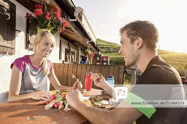 Young couple eating salad at alpine cabin  Kampenwand