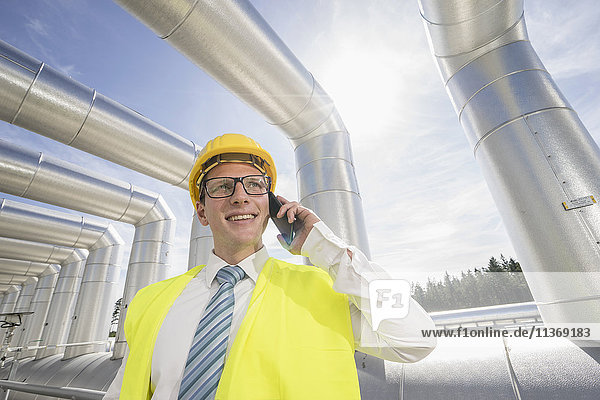Young engineer talking on mobile phone at geothermal power station