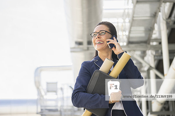 Female engineer talking on mobile phone at geothermal power station
