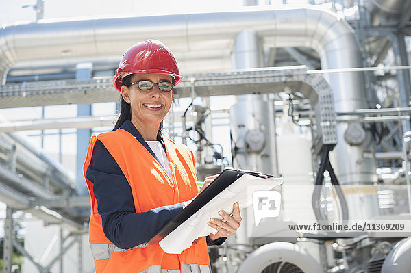 Portrait of a female engineer smiling with document at geothermal power station