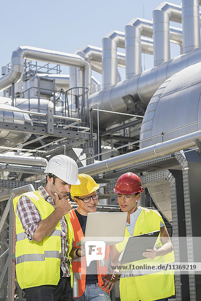 Engineer with his colleagues in meeting with laptop at geothermal power station