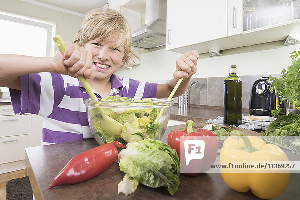 Portrait of a boy preparing salad in kitchen
