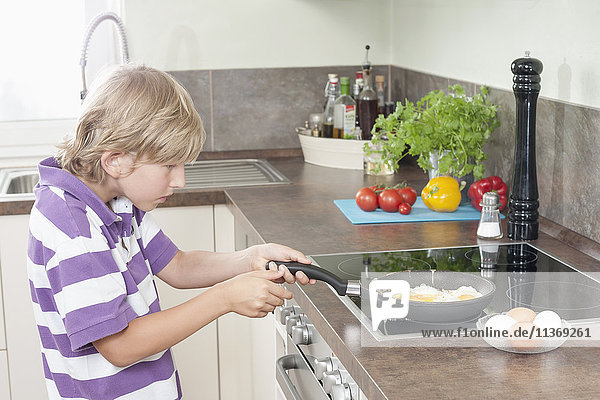 Boy preparing fried eggs in kitchen