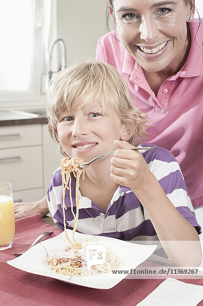 Portrait of a boy eating spaghetti with his mother