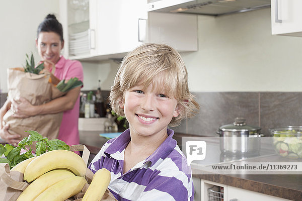 Boy with his mother holding bags of groceries in kitchen