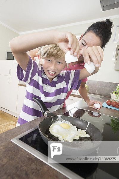 Woman with her son preparing fried eggs in kitchen