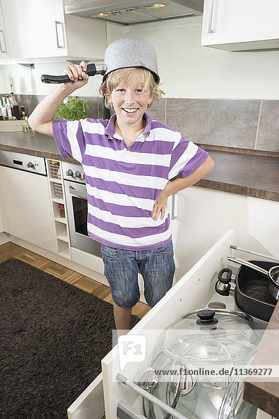 Happy boy with pan on his head in kitchen