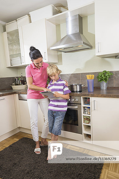 Woman with her son using digital tablet in kitchen