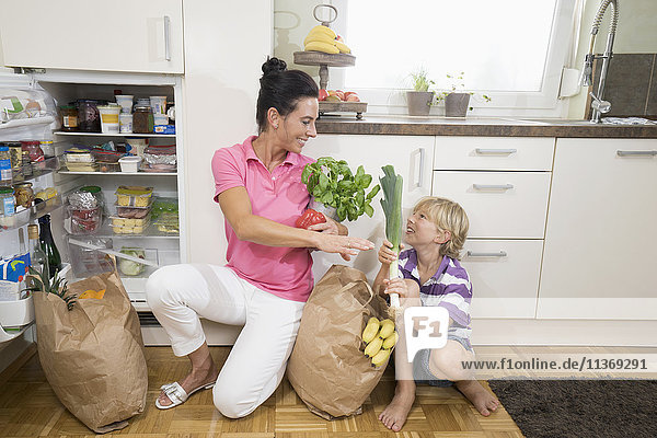 Woman with her son putting grocery shopping in refrigerator