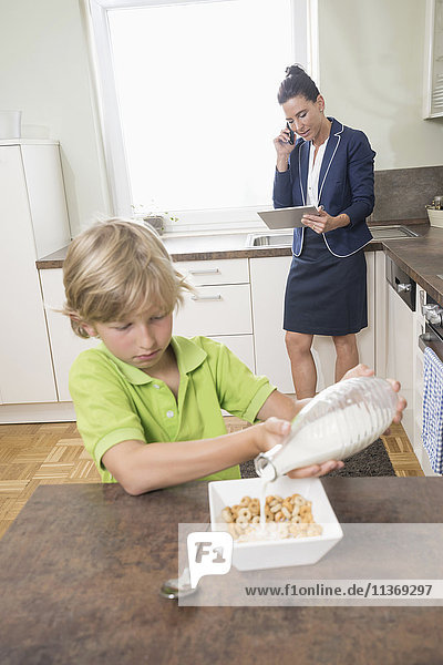 Boy pouring milk in muesli while mother has business call in kitchen