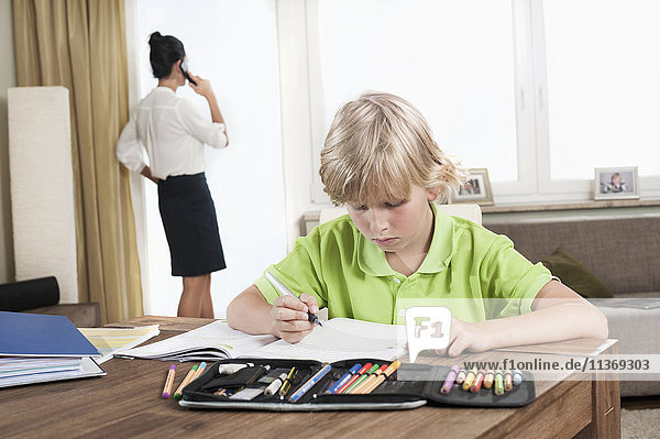Boy studying while mother has business call
