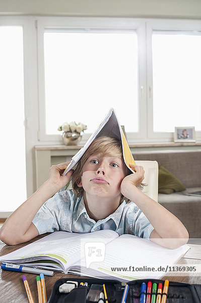 Bored boy with open book on head