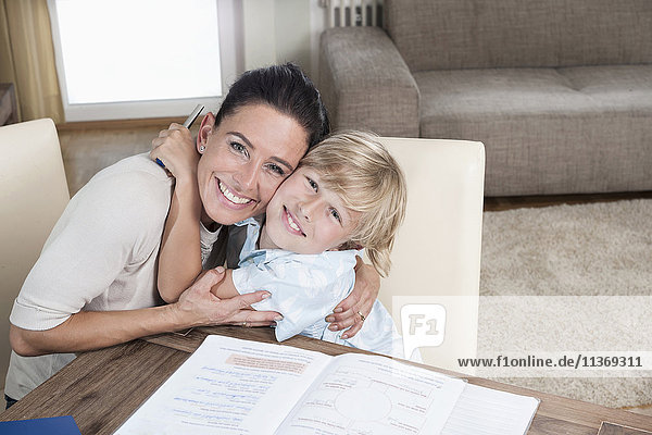 Portrait of a boy embracing his mother while studying