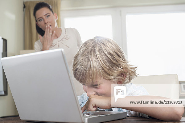 Shocked woman watching her son using laptop in living room