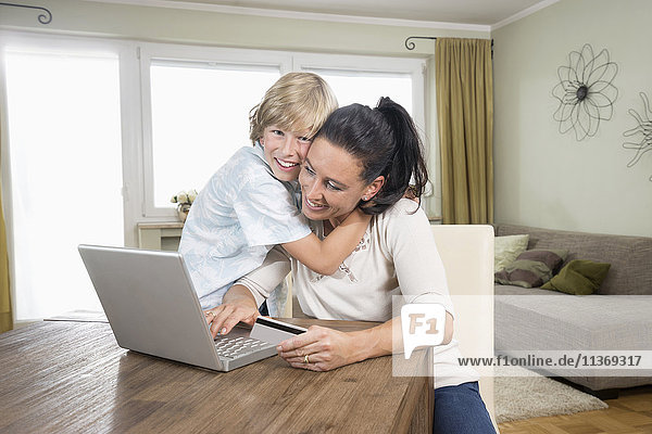 Boy hugging his mother while she online shopping on laptop