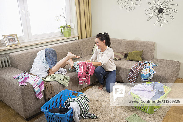 Woman with her son folding laundry in living room