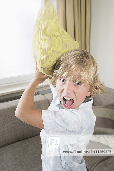 Boy shouting while pillow fighting in living room