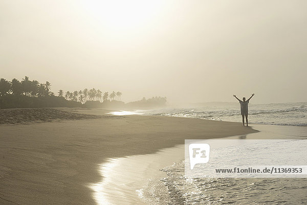 Woman standing with spreading hands on the beach  Tangalle  South Province  Sri Lanka