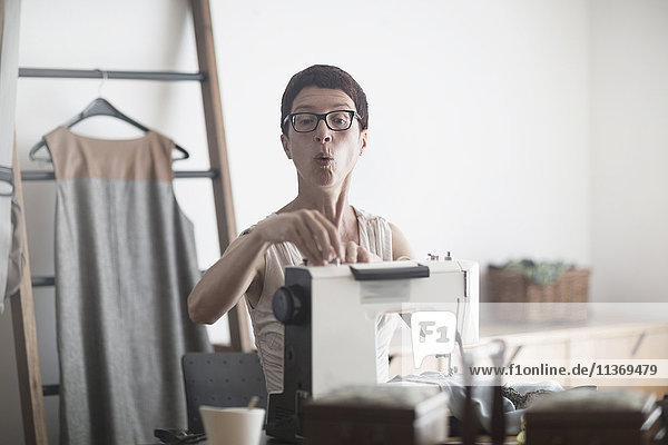 Female dressmaker working on sewing machine