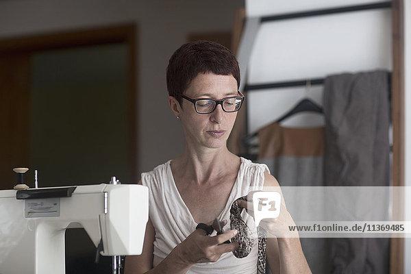 Female dressmaker cutting fabric next to sewing machine