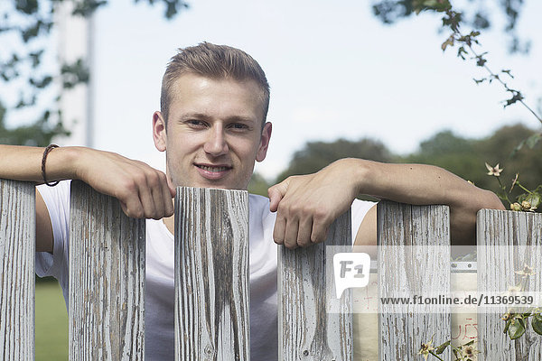 Young man standing by wooden fence in urban garden