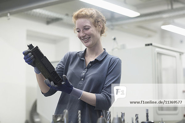 Young female engineer looking at machine part in an industrial plant