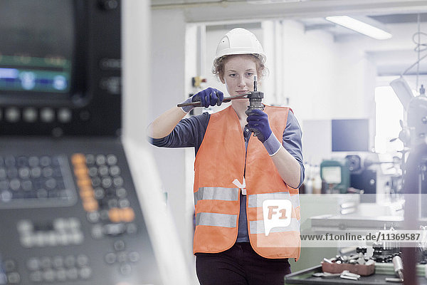 Young female engineer repairing machine part in an industrial plant