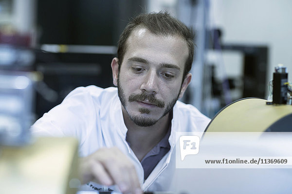 Young male scientist working in technology space