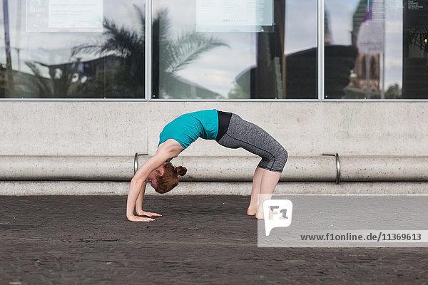 Young woman doing bridge pose on street in urban city