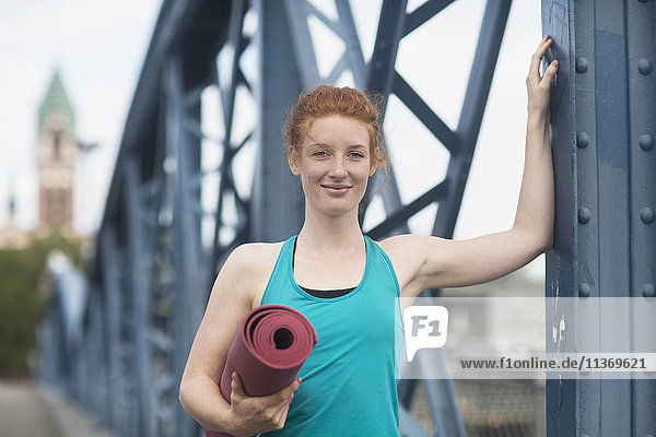 Portrait of a young woman standing with exercise mat in urban city