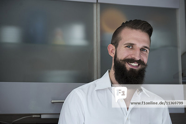 Portrait of a young man standing in the kitchen and smiling