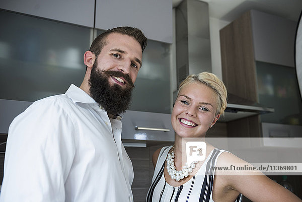 Portrait of a young couple standing in the kitchen