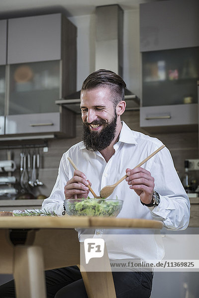 Man preparing salad in the kitchen and smiling