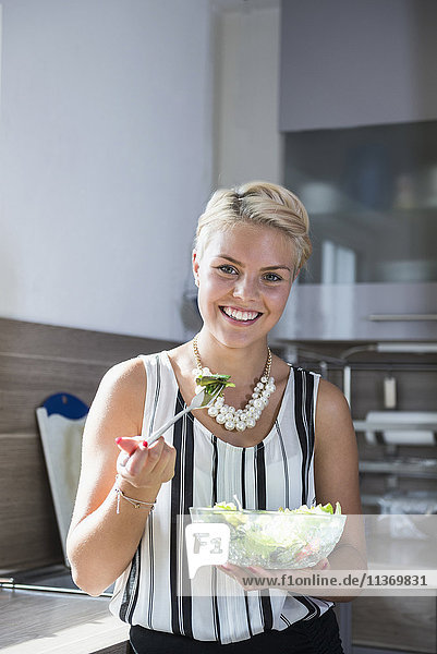 Young woman eating salad in the kitchen and smiling