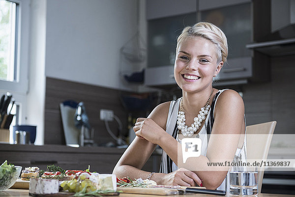 Portrait of a young woman sitting at kitchen table and smiling
