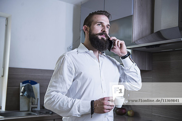 Young man talking on smartphone and drinking coffee in the kitchen