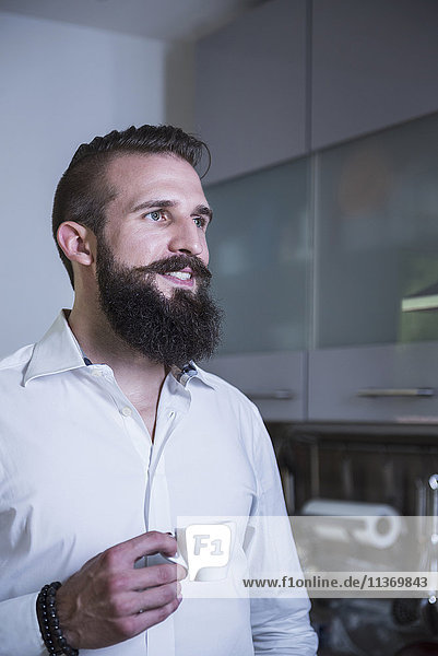 Young man drinking coffee in the kitchen and smiling