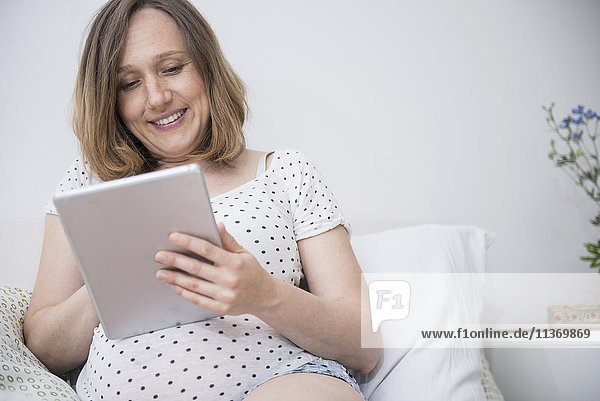 Happy pregnant woman using digital tablet in bed