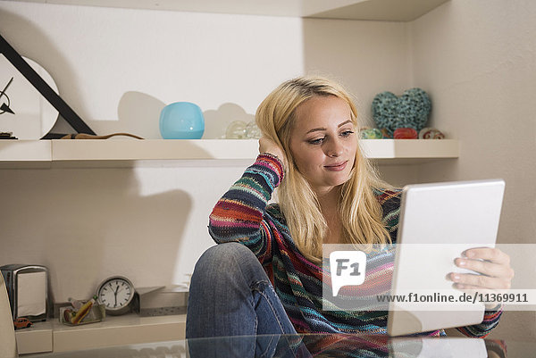 Beautiful young woman using digital tablet in the living room