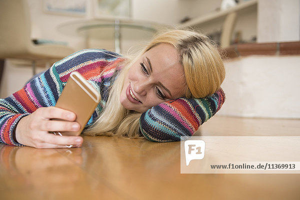 Beautiful young woman using smart phone and lying on floor in the living room