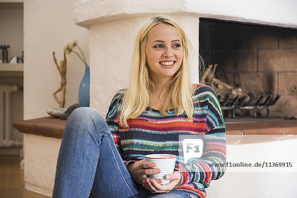 Beautiful young woman having cup of tea and sitting on the floor in front of fireplace in the living room