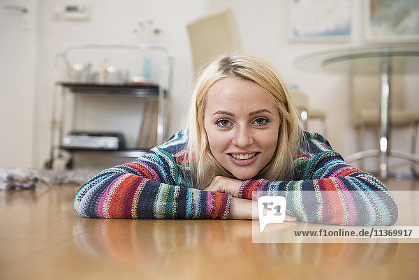 Portrait of a beautiful young woman lying on floor in the living room