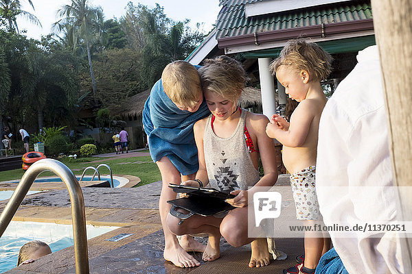 Children with digital tablet at swimming-pool