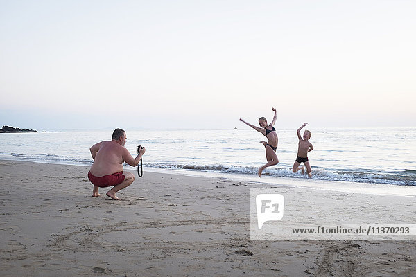 Father taking picture of children on beach