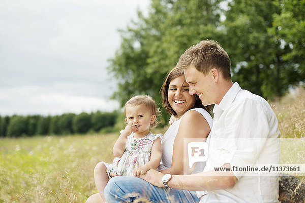 Parents with young daughter sitting in meadow