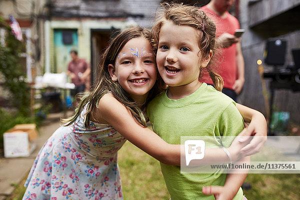 Caucasian girls hugging at backyard party